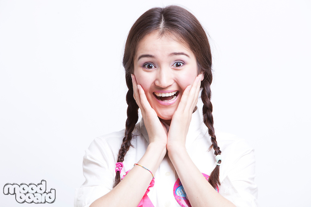 Portrait of surprised young woman with pigtails against white background
