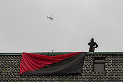 © Licensed to London News Pictures . FILE PHOTO DATED 26/03/2011 of a Black Bloc protester on a roof overlooking Leicester Square at a demonstration in London as reports circulate that black bloc tactics may be employed by protesters seeking to demonstrate during the funeral of former British Prime Minister Margaret Thatcher . Photo credit : Joel Goodman/LNP