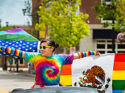 "28 JUNE 2020 - DES MOINES, IOWA: A woman with American and Mexican versions of the Pride Flag participates in the Capitol City Pride Parade in Des Moines. Most of the Pride Month events in Des Moines were cancelled this year because of the COVID-19 pandemic, but members of the Des Moines LGBTQI community, and Capitol City Pride, the organization that coordinates Pride Month events, organized a community ""parade"" of people driving through the East Village of Des Moines displaying gay pride banners and flags. About 75 cars participated in the parade.    PHOTO BY JACK KURTZ"