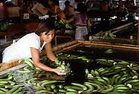 October 1982, San Pedro Sula, Honduras --- A woman washes bananas in a holding tank, San Pedro Sula, Honduras. --- Image by © Owen Franken/CORBIS