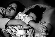 """Alejandra covers Samantha's eyes during a murder scene in the popular late-night soap opera, """"Women Assassins"""" at their home in Belen. They sleep together every night in a twin sized bed clad with Barbie sheets in a room that they share with Alejandra's mom, Deisey and her 12-year-old brother. Deisey has since kicked Alejandra and Samantha out of the house consequential of their frequent fights concerning Deisey's disapproval of Alejandra's job as an exotic dancer in a local discotec. After renting a room for several weeks they moved in with Alejandra's aunt and cousins a few blocks away from her mother's home."""