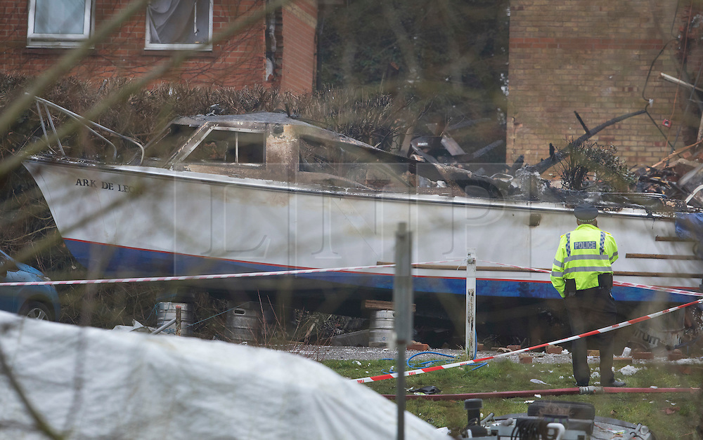© Licensed to London News Pictures. 15/02/2017. Oxford, UK. A policeman looks at a burnt out boat next to the remains of a block of flats damaged in an explosion near Osney Lock in Oxford. A number of people have been injured in what is thought to have been a gas explosion. Photo credit: Peter Macdiarmid/LNP