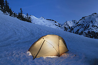 Backcountry camp with tent illuminated at twilight, North Cascades, near Hanneggan Pass, Mount Baker Wilderness Washington