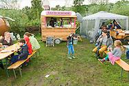 Nederland, Den Bosch, 20140830 <br /> Kinderen en hun ouders eten lekker van de wagen van de Bakblikbende.<br /> Effect Festival - 30 Augustus 2014, De Gemeint 3, bij het Engelermeer tussen Vlijmen en Den Bosch.<br /> eFFect is een manifestatie van lokale duurzame initiatieven die burgers samen van onderop in het leven zetten. Een marktplaats, maar ook workshops door kunstenaars en muziek optredens. Daarnaast ook veel gezonde en alternatieve eettentjes.<br /> <br /> Netherlands, Den Bosch, 20140830.