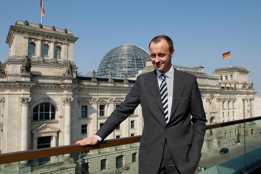 02 APR 2004, BERLIN/GERMANY:<br /> Friedrich Merz, CDU, Stellv. Fraktionsvorsitzender der CDU/CSU Bundestagsfraktion, auf einem Balkon des Jakob-Kaiser-Hauses, im Hintergrund: das Reichstagsgebaeude, Deutscher  Bundestag<br /> IMAGE: 20040402-01-034<br /> KEYWORDS: Reichstag