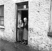 Mrs. Bridget O'Riordan and Mrs. Mary Kelly standing at the door of their rooms at the Corporation Widows Alms House, Limerick..28.03.1962.<br />