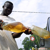 Benin november 28, 2001 - Young man with his little petrol station in Cotonou, this petrol and diesel are smuggled from Nigeria. Nigerian oil compagnies are incapable of halting these parallel imports of petroleum. For many peoples, It's just a job and to try to survive