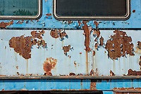 Swirled rust patterns on the side of an old,abandoned bus.