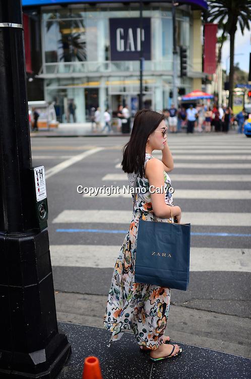Asian woman waiting in crosswalk at Hollywood Boulevard.