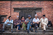 Nepali men sit and chat in front of a temple wall in Durbar Square.