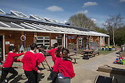 Children running in the playground of Botley primary school, Low carbon hub have helped them get solar PV panels on the roof. <br /> Low Carbon Hub, Oxford. A community energy hub developing community owned renewable energy projects across Oxfordshire.  ALL publication MUST include the credit © Andrew Aitchison / ASHDEN.