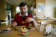 Chris McCarthy, astronomer, having his dinner in the dining hall of the Lick Observatory on Mt. Hamilton. San Jose, California. Chris stays at the observatory for 4 nights in a row. The cook, Dennise Casey, makes him a 'night lunch' (in paper bag) every evening since he works all night at the 120-inch telescope. His night lunch consists of 2 sandwiches, fruit, potato or corn chips and 3 cookies. Chris is a vegetarian.  Exoplanets & Planet Hunters