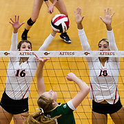 18 November 2017:  The San Diego State women's volleyball team closes out it's season against #24 Colorado State University. San Diego State middle blocker Baylee Little (16) and outside hitter Alexis Cage (18) attempt to block a spike by a CSU player in the first set. The Aztecs fell to the Rams in three sets. <br /> www.sdsuaztecphotos.com