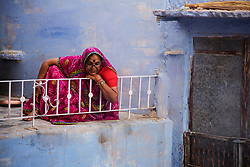 A woman in colorful sari sitting in front of her home in the blue city of Jodphur, Jodphur, Rajasthan, India,