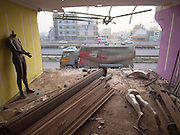 "Yelahanka, Karnataka, India - <br /> <br /> India's Rocky Road<br /> <br /> India, with the second largest road network in the world, is on a massive, nationwide road building campaign, cutting shops and houses in half to make way for the roads. My work shows those houses and shops, after they are cut right up to the point where the newly expanded highway and service roads will be. The structures are not cut any further in order to minimize the costs of the demolition and to allow the building inhabitants to continue to use the remainder of the space.<br /> <br /> Road building in the Indian subcontinent can be traced back to 4000 BC and has included such famous highways as the Grand Trunk Road, stretching 1,600 miles from modern-day Bangladesh to Pakistan. Up through India's independence in 1947, to 1988, most Indian roads were just a single lane, a system once ranked worse than Botswanas, by the World Economic Forum.Since liberalization of the Indian economy in 1995, the National Highways Authority of India has privatized road development in India, and has directed the building of over 44,000 miles of new highways (as of December of 2012.) Of those, 11,800 miles are 4-lane or 6-lane modern highways.Another 24,900 miles of widened roads are in the planning stages.<br /> <br /> Most people whose buildings have been cut have been compensated by the government (or they were on the land illegally and were denied such compensation.) While many structures have been completely demolished, the remaining half-cut buildings are what have caught my attention.  In these, the cuts are almost ""surgical"" in their precision, yet in this case, the ""surgeons"" couldn't care less about their ""patients.""<br /> <br /> I have been photographing the impact of globalization across India for almost two decades. I am particularly intrigued by this topic because, unlike so much of my previous work on globalization, the 'before and after' are visible in just one frame. You can see both the expressway that is consuming the land and the mutil"