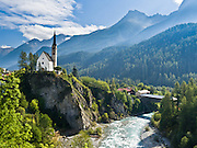 """An old covered bridge crosses the En River near the main church in Scuol (or Schuls), Lower Engadine, Grison Alps, Switzerland, Europe. Scuol is the terminal station of the """"Rätische Bahn"""" (RhB). The Swiss valley of Engadine translates as the """"garden of the En (or Inn) River"""" (Engadin in German, Engiadina in Romansh, Engadina in Italian). Published in """"Light Travel: Photography on the Go"""" by Tom Dempsey 2009, 2010."""
