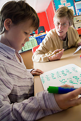 Girl sitting at desk in classroom practising writing skills; with teacher watching,