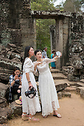 Two Chinese women take a selfie photo of themselves dressed in white bridal dresses in the ancient ruins of Angkor Thom, Siem Reap Province, Cambodia, South East Asia. Another woman sits on the stones and checks her phone.  (photo by Andrew Aitchison / In pictures via Getty Images)