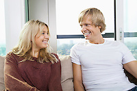Cheerful couple sitting on sofa and looking at each other at home