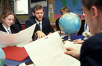 Secondary geography lesson with teacher showing students a world globe.
