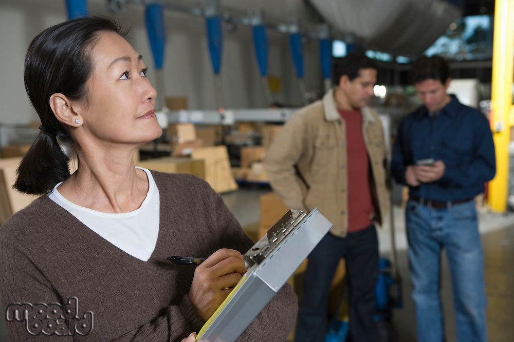 Asian woman making notes in distribution warehouse