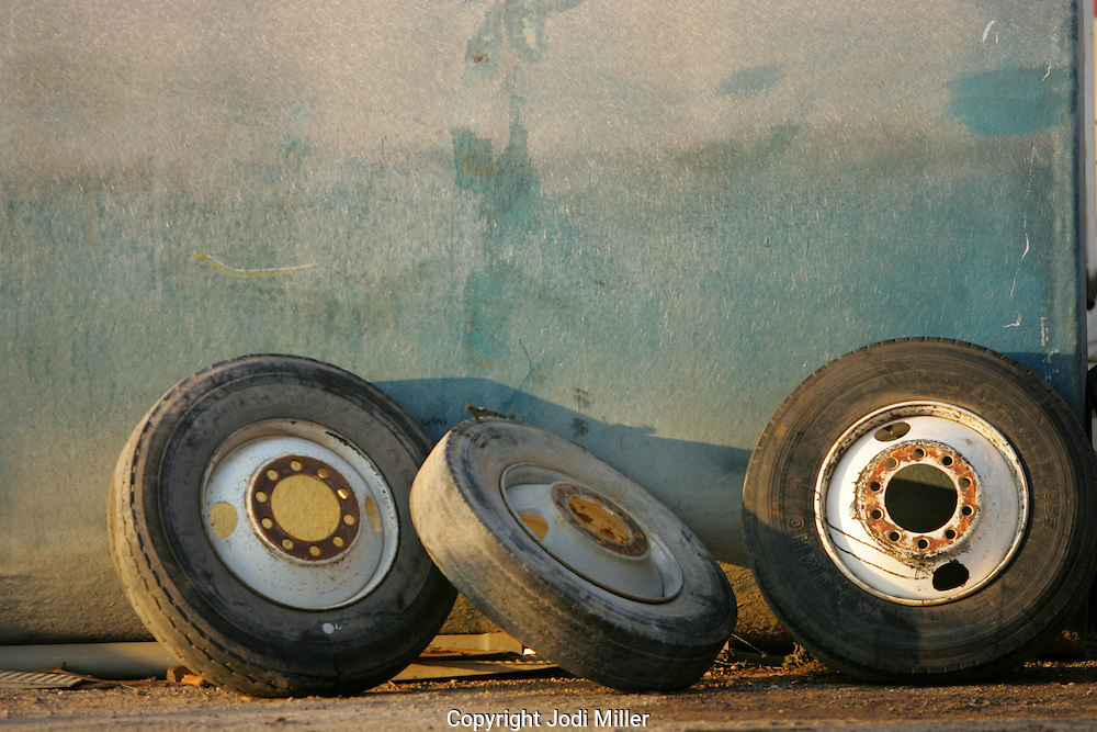 Three old tires against a blue wall.