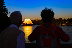 Tourists photograph artist Christo's 'Mastaba', an installation made up of over 7,000 barrels floating on The Serpentine in London's Hyde Park catches the setting sun and reflects it on the water. London, July 02 2018.
