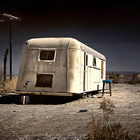 An old white caravan left to rot in the desert
