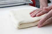 Making puff pastry at a bakery baker folds the dough
