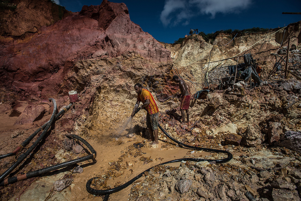 """LAS CLARITAS, VENEZUELA - JULY 20, 2016:  Carlos Freydel, 26, (right) mines for gold at """"Cuatro Muertos"""" mine outside of Las Claritas.  Freydel said he has fallen ill with malaria 60 times during the 9 years he has worked illegally mining for gold. When he gets malaria, it usually keeps him from being able to work in the mine for a full week.  Even though he has suffered so much from malaria, """"it is worth it, because there is money here,"""" he said.  He mistakingly thinks that he gets malaria from the water, and did not believe visiting journalists that said he gets it from being bit by mosquitos.  Thousands of Venezuelans are flocking to illegal gold mines, like this one, in hopes of surviving the current economic crisis by earning in gold instead of the national currency, whose value steadily falls due to the world's highest inflation.  From this remote part of the jungle the migrant miners have become the vectors of a new epidemic of malaria, because the hot, swampy conditions of the mines make for an ideal breeding ground for mosquitos. Miners spread the disease as they return home with earnings or pay visits to family members. The economic crisis has also left the government without the financial resources to control the disease - they are unable to fumigate homes, provide medicines to everyone that is sick, or even to test all patients with symptoms of malaria in many places. PHOTO: Meridith Kohut for The New York Times"""