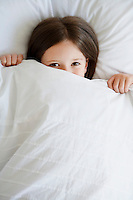 Little girl in bed pulling covers over face portrait high angle view