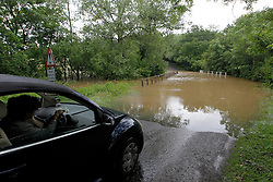 © Licensed to London News Pictures. 11/06/2012, Petworth, UK.  A driver stops at the edge of a flooded road near Petworth, West Sussex, England as continuous rain cause flooding to many area, Monday, June 11, 2012. Photo credit : Sang Tan/LNP