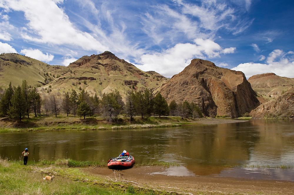 Woman, dog and raft on the John Day River at Cathedral Rock, northeastern Oregon.