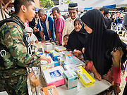 14 JUNE 2015 - NARATHIWAT, NARATHIWAT, THAILAND: Thai Muslims talk to Thai army medics during a food distribution event in Narathiwat. The food distribution happens every year before Ramadan, which starts June 18. The annual food distribution event is organized by the Southern Peace Media Club, a group of Thai journalists who work in the southern provinces of Pattani, Narathiwat and Yala. An insurgency pitting Muslim extremists against the Thai government has rocked Thailand's southern three provinces since 2001. More than 6,000 people have been killed in the sectarian violence.    PHOTO BY JACK KURTZ