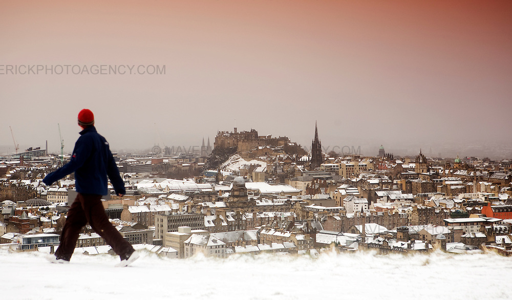 A man walks across the Edinburgh Crags looking at the view of the city covered in snow.  Heavy snow has fallen across large parts of the UK, disrupting travel and closing thousands of schools.  Weather warnings of heavy and drifting snow are also in place for many southern and eastern parts of Scotland.