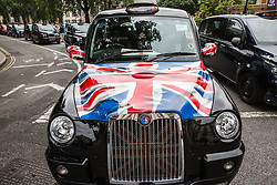 London, UK. 26 June, 2019. Licensed taxi drivers, or black cab drivers, block Parliament Square as part of a protest against restrictions imposed on licensed taxis.