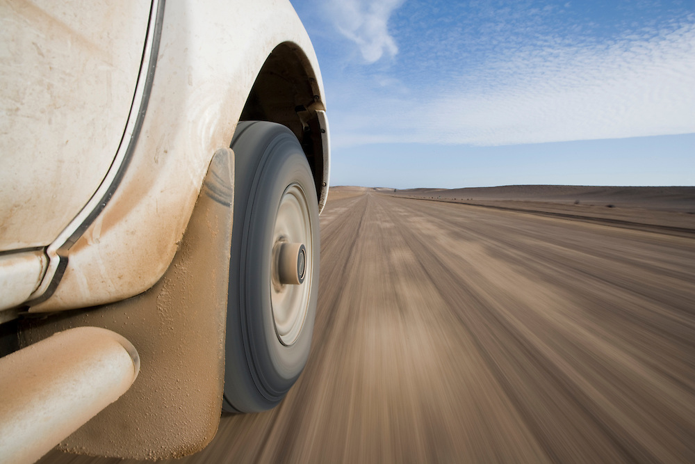Africa, Namibia, Skeleton Coast, Low-angle view of safari truck driving on dirt road along Skeleton Coast