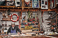 A craftsman works on a sailboat at the Sequana Boat Club in Chatou, France. Just outside the door is the Seine River.  Aspect Ratio 1w x 0.667h.
