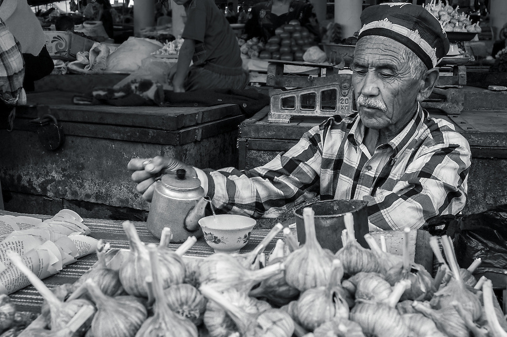 Portrait of an old Tajik man pouring a cup of tea behind a pile of garlic bulbs in a market in western Tajikistan
