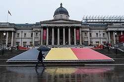 © Licensed to London News Pictures. 24/03/2016. London, UK. A 25m silk Belgian flag is laid out on the steps in Trafalgar Square as a tribute to those who lost their lives in the recent bombings in Brussels.  Visitors are expected to attend a vigil to lay flowers and candles to pay their respects. Photo credit : Stephen Chung/LNP