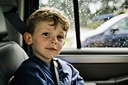 Young boy, age four, with seatbelt in the back seat of a car.