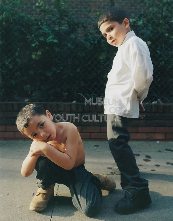 Two young boys posing together on the pavement.