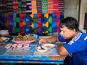 "11 JUNE 2015 - MAHACHAI, SAMUT SAKHON, THAILAND: A Burmese migrant worker eats his lunch during a break at the Samut Sakhon shrimp market in Mahachai. Labor activists say there are about 200,000 migrant workers from Myanmar (Burma) employed in the fishing and seafood industry in Mahachai, a fishing port about an hour southwest of Bangkok. Since 2014, Thailand has been a Tier 3 country on the US Department of State Trafficking in Persons Report (TIPS). Tier 3 is the worst ranking, being a Tier 3 country on the list can lead to sanctions. Tier 3 countries are ""Countries whose governments do not fully comply with the minimum standards and are not making significant efforts to do so."" After being placed on the Tier 3 list, the Thai government cracked down on human trafficking and has taken steps to improve its ranking on the list. The 2015 TIPS report should be released in about two weeks. Thailand is hoping that its efforts will get it removed from Tier 3 status and promoted to Tier 2 status.        PHOTO BY JACK KURTZ"