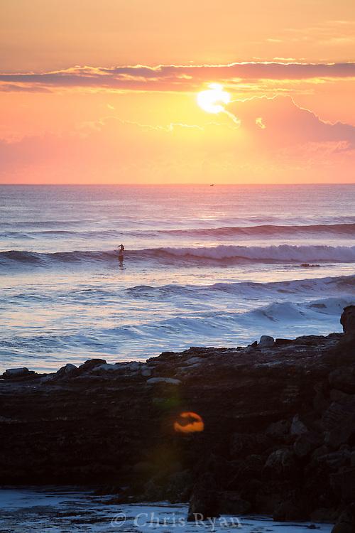 Surfer catching a wave at sunset in Santa Cruz, California