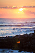 Surfer catching a wave at sunset in Santa Cruz, California