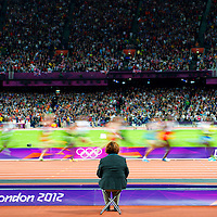 An Olympic track official monitors the last lap of the 10,000 meter race during the 2012 London Summer Olympics.  British runner Mo Farah was the gold medal victor with a time of 27 minutes 30.42 seconds.