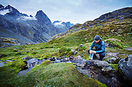 A hiker purifies some drinking water from a high alpine stream in the Talkeetna Mountains of Alaska backcountry.