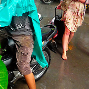 Western tourist walking at Hanoi street during rain