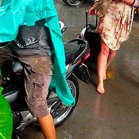 Western tourist walking at Hanoi street during rain