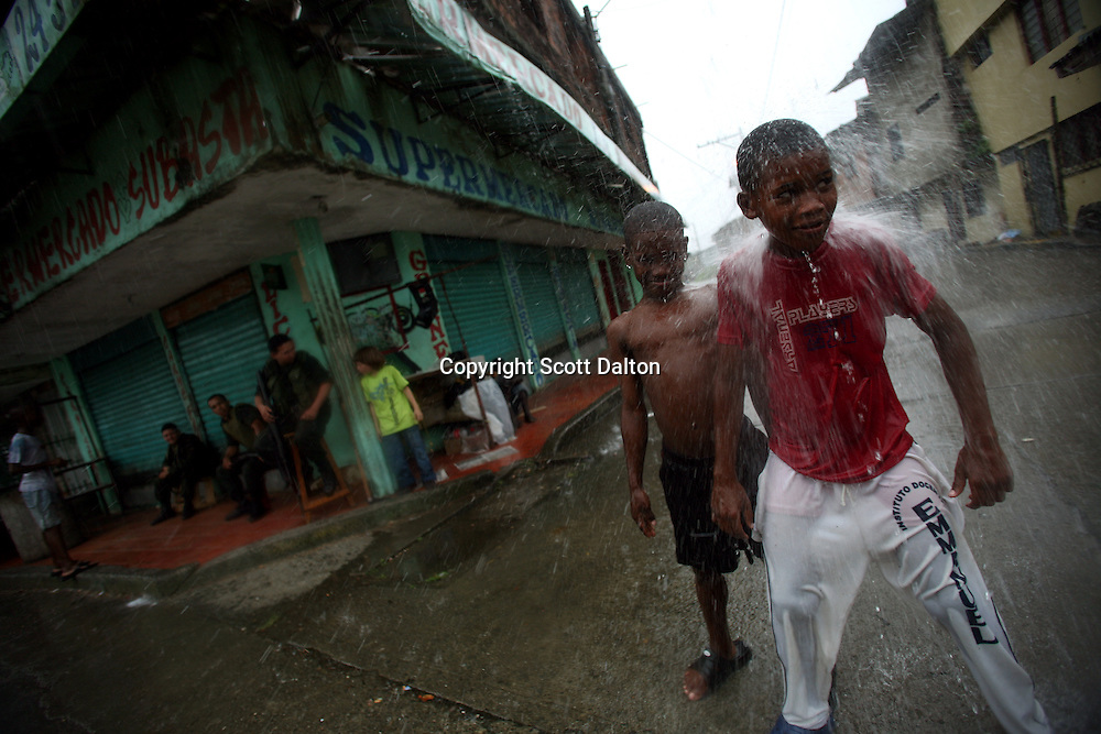 Boys play in the water runoff during a rainstorm in Lleras, a poor barrio in Buenaventura, on the Pacific Coast of Colombia, on Sunday, May 13, 2007. Buenaventura is in the midst of a spree of violence over control of drug shipments from the poor barrios in the city. Many of the neighborhoods have a strong presence of FARC militias that control most of the drug trade in the city. (Photo/Scott Dalton)